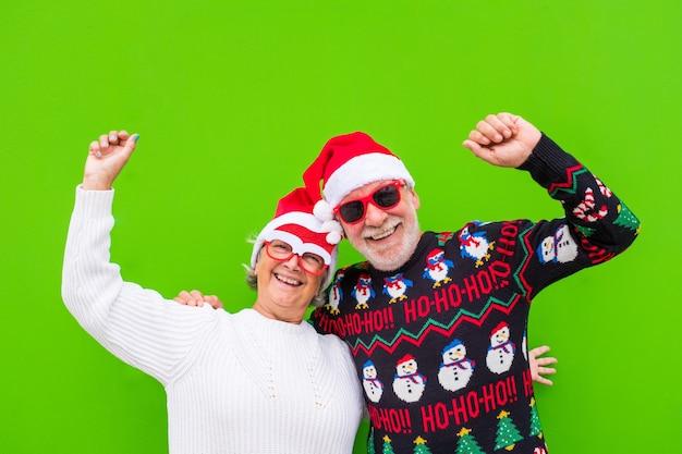 Retrato de casal de dois idosos e pessoas maduras e velhas se divertindo, curtindo o dia de natal juntos, vestindo roupas de natal e com fundo verde colorido.
