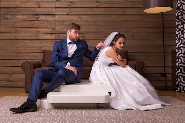 Retrato de casal de família briga, sentado na mesa da sala de madeira