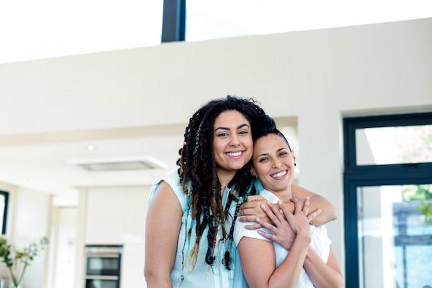 Retrato de casal de lésbicas, abraçando-se na sala de estar