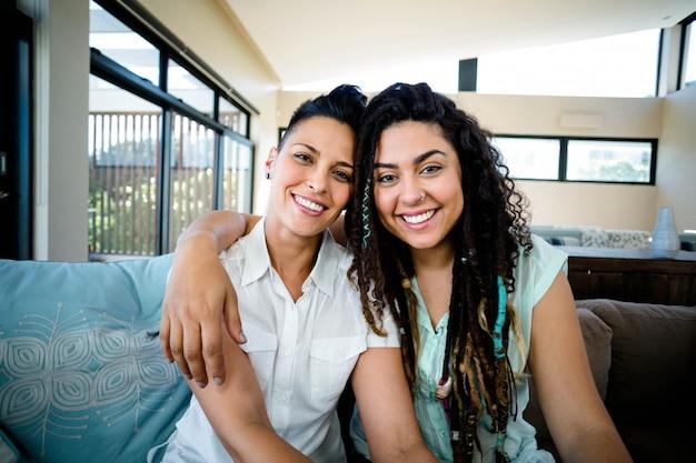 Retrato de casal de lésbicas feliz abraçando e sorrindo na sala de estar