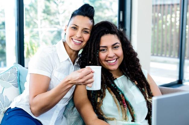 Retrato de casal de lésbicas feliz tomando café e usando o laptop na sala de estar