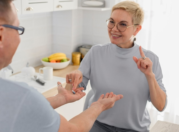 Retrato de casal de meia-idade tomando comprimidos antes do jantar - cuidados de saúde para idosos