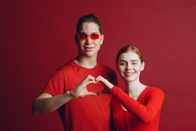 Retrato de casal de namorados sorrindo e abraçando, fazendo a forma de um sinal de coração com as mãos. dia dos namorados