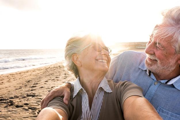 Retrato de casal de pessoas maduras e velhas aproveitando o verão na praia, olhando para a câmera, tirando uma selfie junto com o pôr do sol ao fundo. dois idosos ativos viajando ao ar livre.