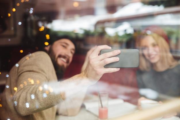 Retrato de casal engraçado no café por trás do vidro