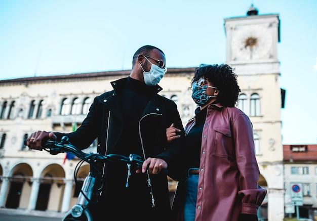 Retrato de casal étnico negro com máscara protetora e bicicleta.