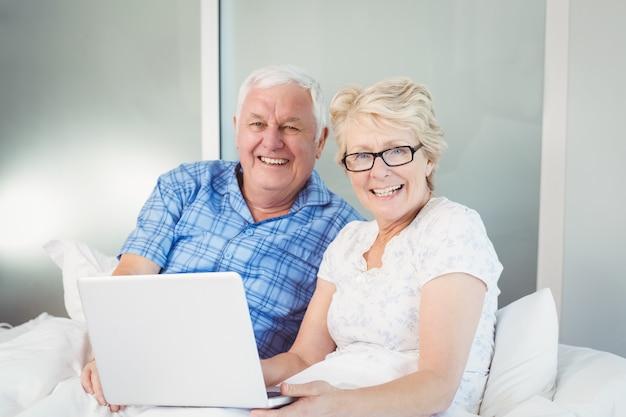 Retrato de casal feliz com o laptop na cama