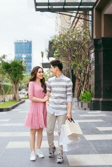 Retrato de casal feliz com sacolas de compras depois de fazer compras na cidade
