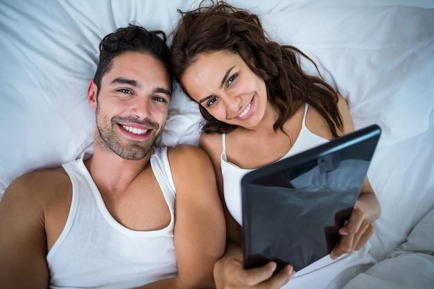 Retrato de casal feliz com tablet digital, deitada na cama
