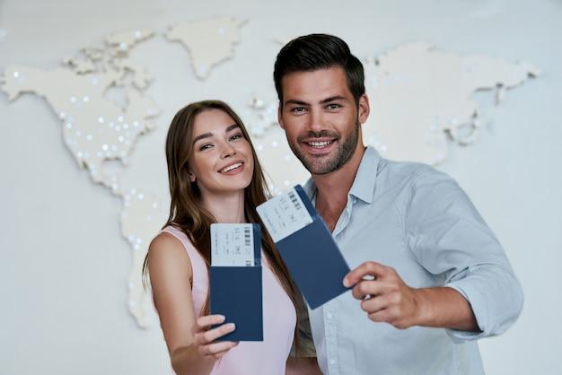 Retrato de casal feliz e alegre segurando um passaporte com bilhetes de avião nas mãos
