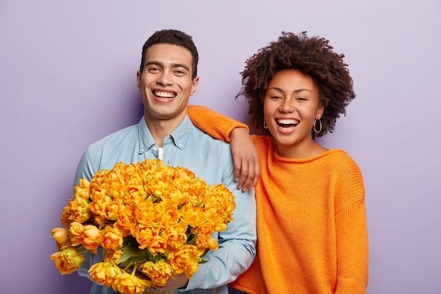 Retrato de casal feliz e buquê de flores