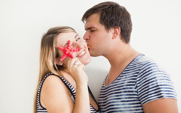 Retrato de casal feliz e sorridente posando com estrela do mar vermelha