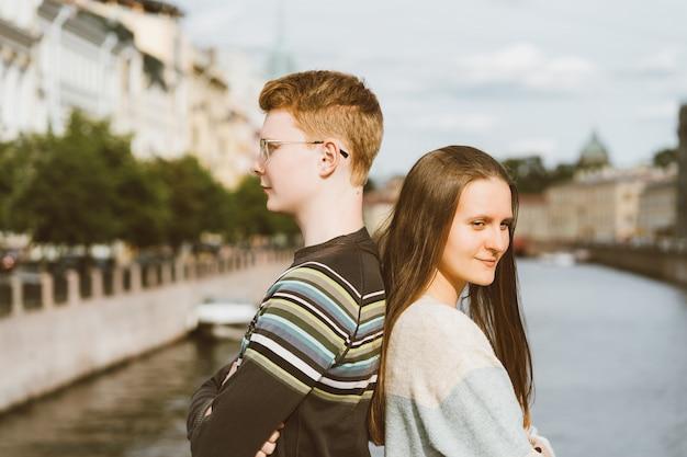 Retrato de casal feliz, em pé de costas no centro da cidade, homem ruivo