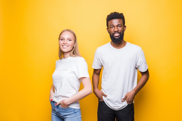 Retrato de casal feliz multirracial se abraçando e posando juntos sobre uma parede amarela em estúdio