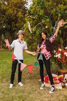 Retrato de casal feliz na árvore de natal no parque. jovem casal decora a árvore de natal.