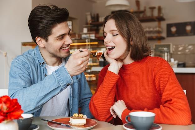 Retrato de casal feliz namorando, enquanto homem alimentando mulher com bolo saboroso em uma padaria aconchegante