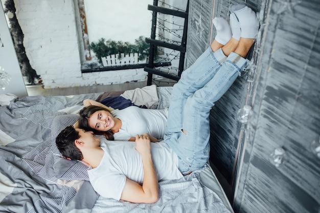 Retrato de casal feliz relaxando na cama e segurando as mãos e pernas pela manhã