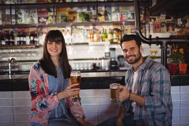 Retrato de casal feliz segurando copos de cerveja no balcão