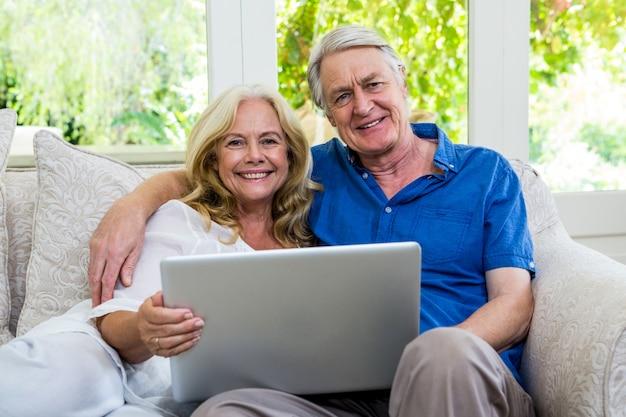Retrato de casal feliz sênior com laptop em casa