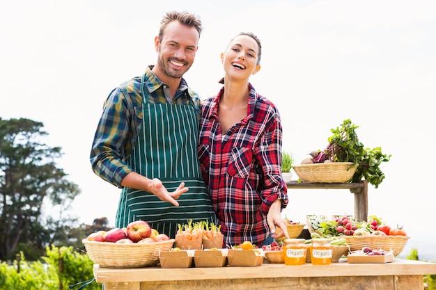 Retrato de casal feliz vendendo legumes orgânicos