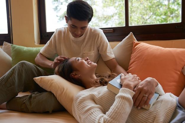 Retrato de casal fofo passar o fim de semana lendo um livro no sofá, menina deitada nos joelhos do namorado