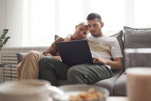 Retrato de casal gay contemporâneo na vida cotidiana, dois jovens usando laptop juntos enquanto relaxam no sofá em casa, copie o espaço