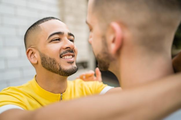 Retrato de casal gay feliz passando um tempo juntos e se abraçando na rua