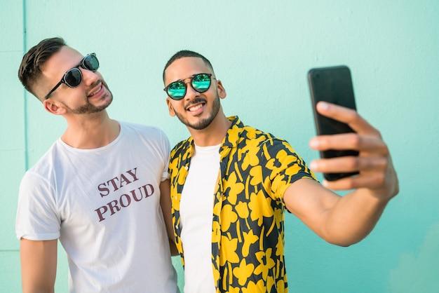 Retrato de casal gay feliz, passando um tempo juntos e tirando uma selfie com o celular. conceito de lgbt e amor.