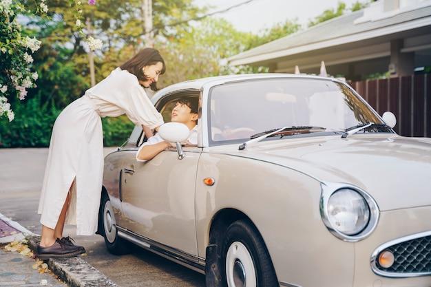Retrato de casal hippie com carro clássico. amor no conceito de viagem rodoviária.
