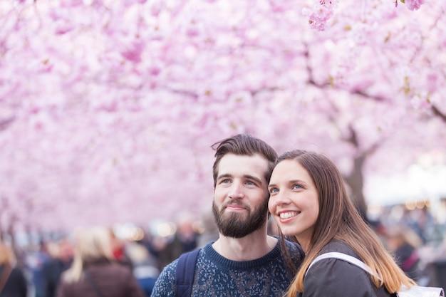 Retrato de casal hipster em estocolmo com flores de cerejeira