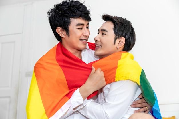 Retrato de casal homossexual asiático abraço e segurando a mão com bandeira do orgulho no quarto