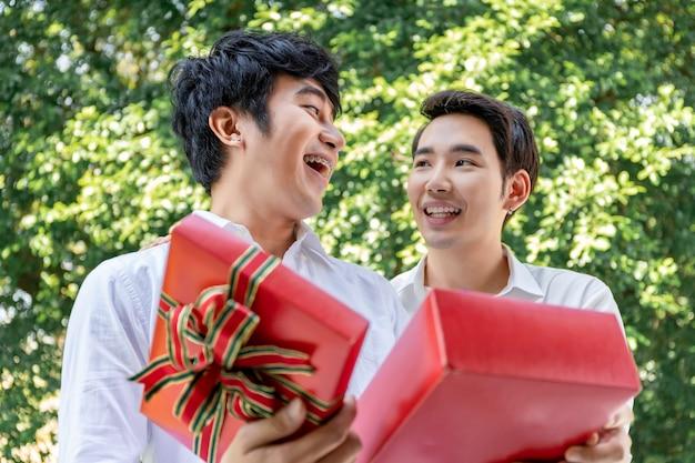 Retrato de casal homossexual asiático abraço e surpresa caixa de presente para namorado