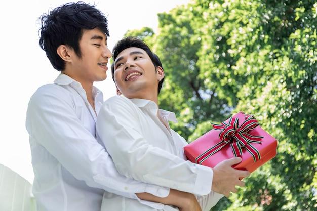 Retrato de casal homossexual asiático abraço e surpresa caixa de presente para o namorado. conceito lgbt gay.