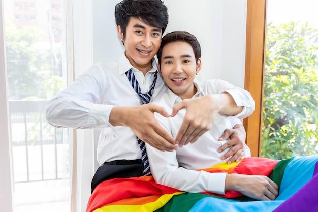 Retrato de casal homossexual asiático as mãos em forma de coração de amor