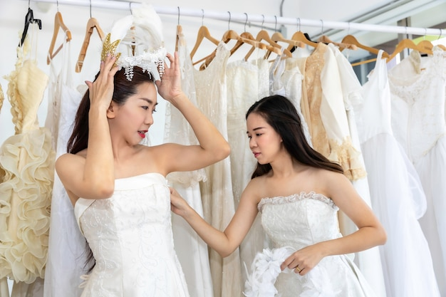Retrato de casal homossexual asiático no vestido de noiva, escolhendo o vestido em uma loja. lésbica de lgbt conceito.