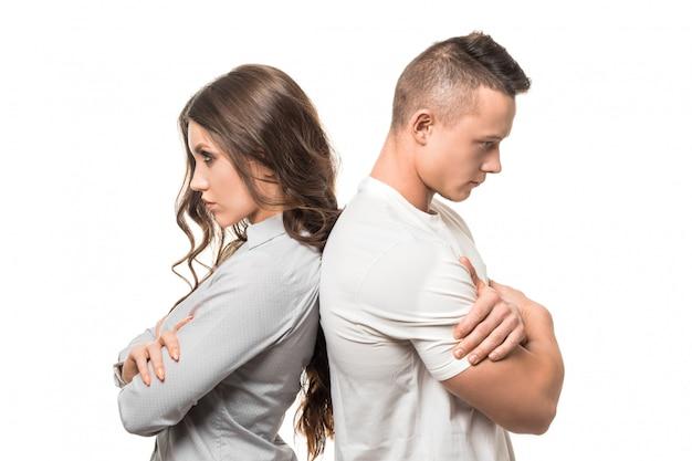 Retrato de casal infeliz chateado em pé de costas segurando os braços cruzados, ignorando-se isolado na parede branca