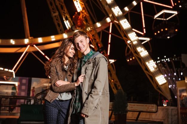 Retrato de casal jovem alegre em parque de diversões.