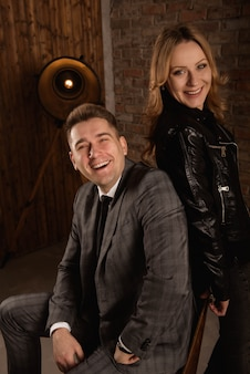 Retrato de casal jovem bonito de terno e jaqueta de couro, abraçando e sorrindo