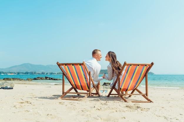 Retrato de casal jovem feliz, abraçando-se perto com espreguiçadeiras no hotel de praia de luxo