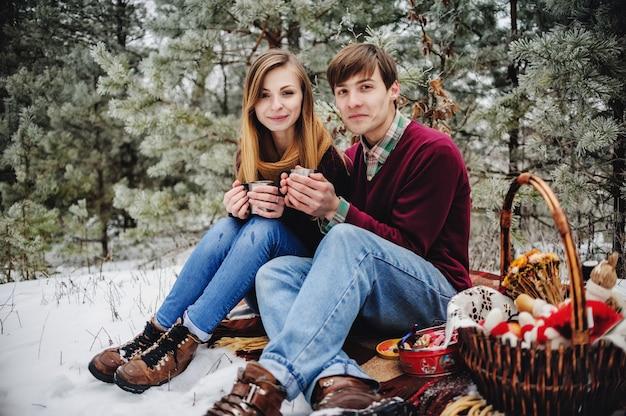 Retrato de casal jovem feliz no piquenique no dia dos namorados em um parque nevado. homem e mulher bebem vinho quente, chá quente e café na floresta. feriado de natal, celebração. feliz ano novo.