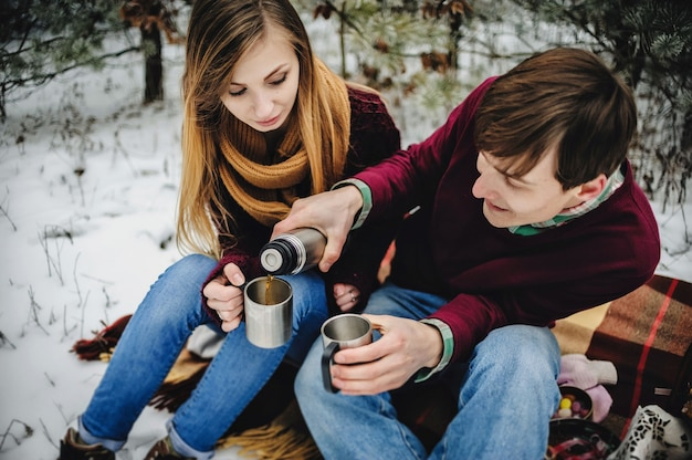 Retrato de casal jovem feliz no piquenique no dia dos namorados em um parque nevado. homem e mulher se derramam em xícaras de vinho quente, chá quente e café com garrafa térmica. feriado de natal, celebração.