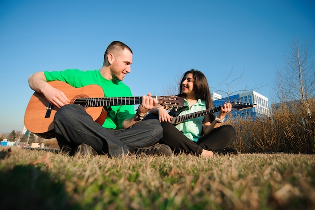 Retrato de casal jovem romântico tocando guitarra sob o céu azul.