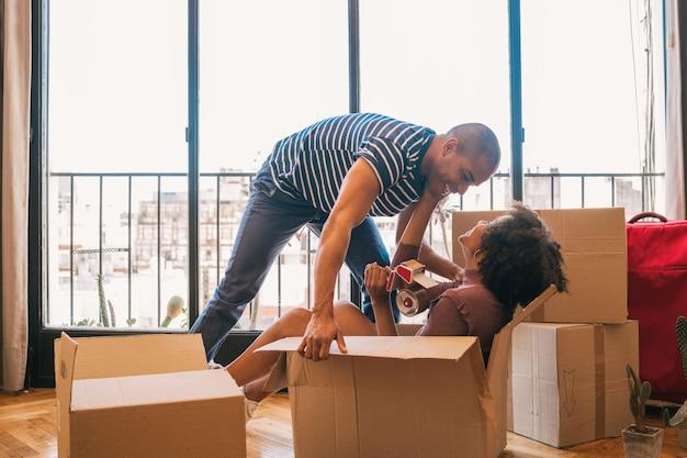 Retrato de casal latino feliz se divertindo com caixas de papelão na casa nova no dia da mudança. conceito imobiliário.