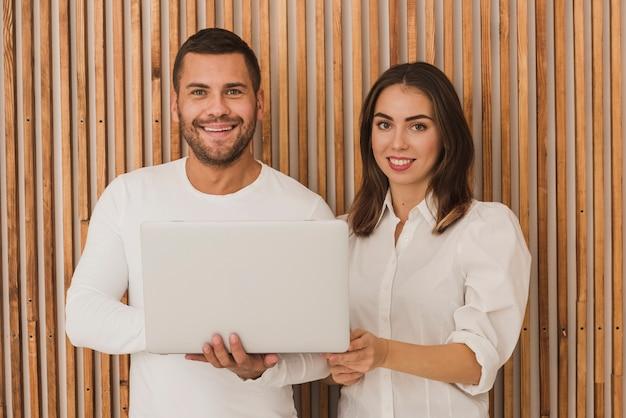 Retrato de casal lindo com um laptop