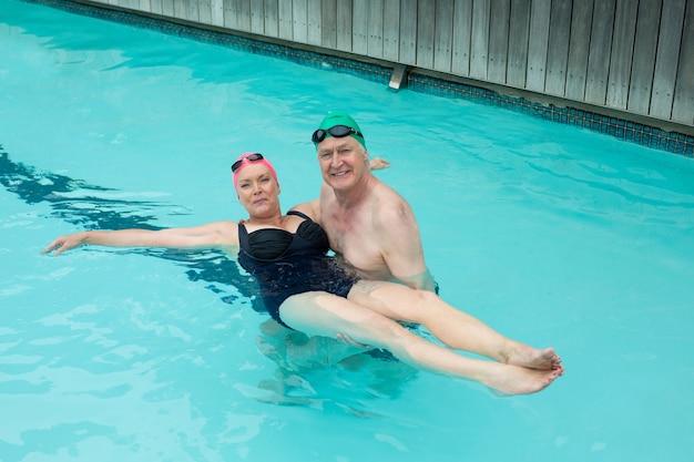 Retrato de casal maduro apaixonado, desfrutando de uma piscina