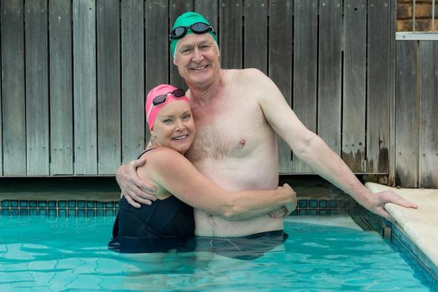 Retrato de casal maduro se abraçando na piscina