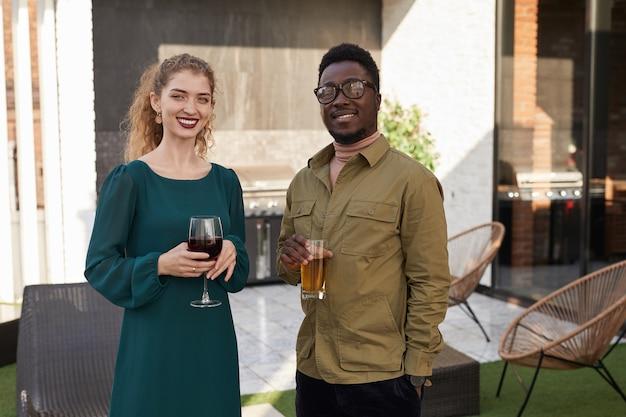 Retrato de casal mestiço contemporâneo com a cintura para cima enquanto saboreia um vinho em pé no terraço ao ar livre.