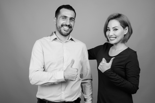 Retrato de casal multiétnico juntos e apaixonados em cinza em preto e branco