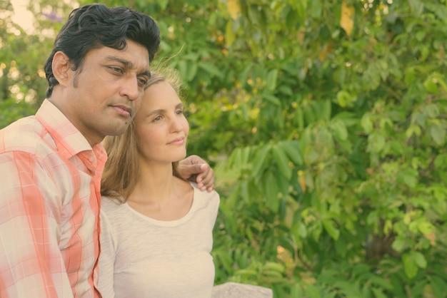 Retrato de casal multiétnico juntos e apaixonados em um parque tranquilo ao ar livre