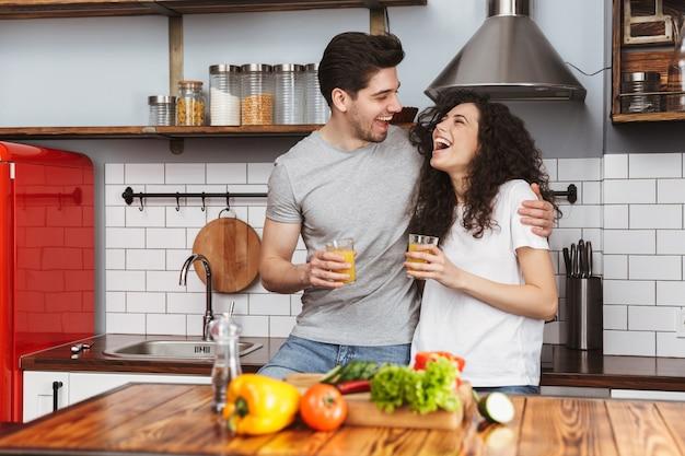Retrato de casal otimista, homem e mulher, cozinhando salat com legumes juntos, enquanto tomam café da manhã na cozinha de casa